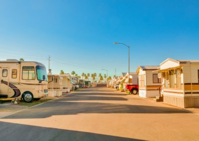 Photograph of the RV park grounds at Garden Oasis RV Resort. There's a paved road in the middle of the image, RV trailers can be seen on either side of the street. Some cars are parked in the driveways of the RV sites. Palm trees can be seen in the background.