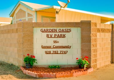 """The sign at Garden Oasis RV Resort with a description of the park, The sign reads """"Garden Oasis RV Park 55+ Senior Community 928 782 7747."""""""
